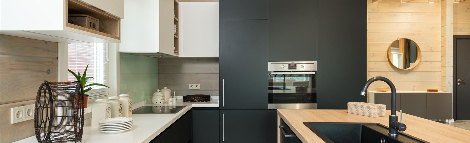 Kitchen with reflective backsplashes and small circular mirror